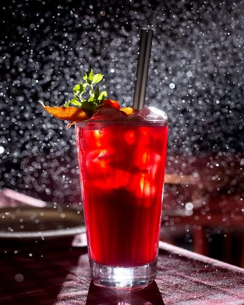 Een glas rode cocktail gegarneerd met stukjes sinaasappel in een donkere achtergrond met licht Gratis Foto