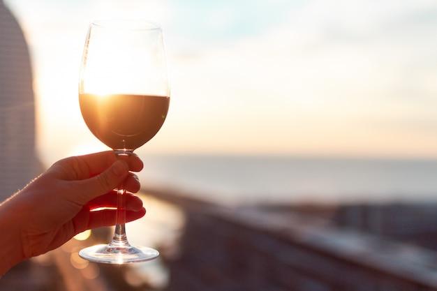Een glas rode wijn bij zonsondergang. Premium Foto
