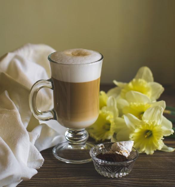 Een glas schuimige latte versierd met narcis Gratis Foto