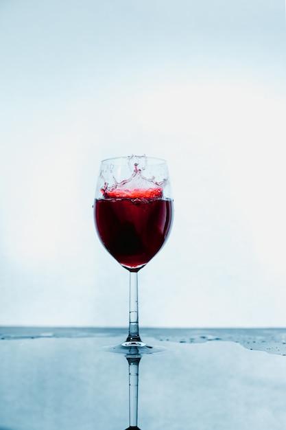 Een glas waarin rode wijn op abstracte achtergrond wordt gegoten. Premium Foto