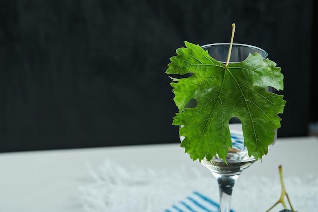Een glas wijn met blad op witte lijst Gratis Foto