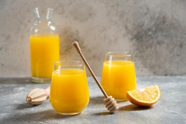 Een glazen bekers sinaasappelsap en een houten lepel. Gratis Foto