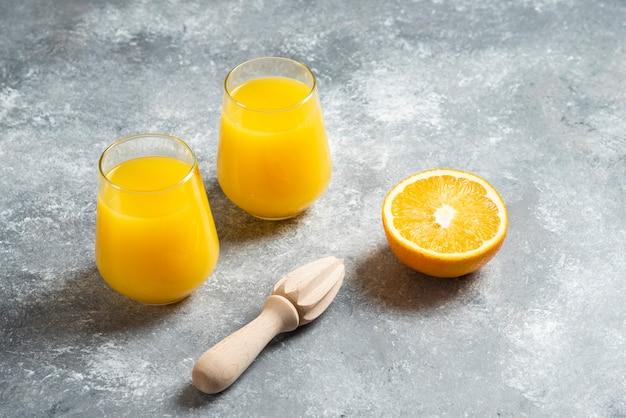 Een glazen bekers sinaasappelsap en een houten ruimer. Gratis Foto
