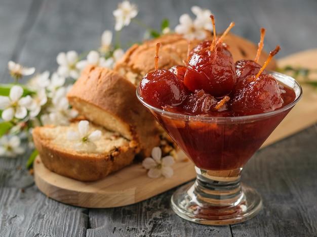 Een glazen kom met hele appeljam en een verse cake op een houten tafel. zelfgemaakte zoetigheden volgens oude recepten. Premium Foto