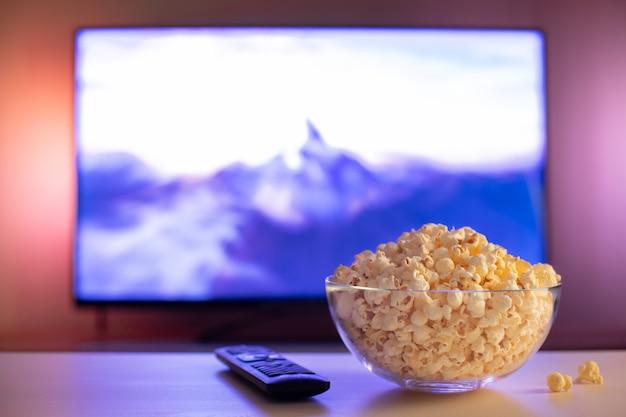Een glazen kom popcorn en afstandsbediening. Premium Foto