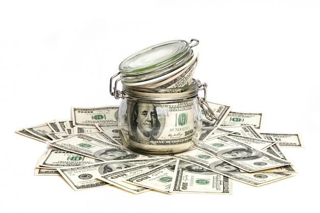 Een glazen pot gevuld met dollars onder honderd-dollarbiljetten op een witte achtergrond. Premium Foto