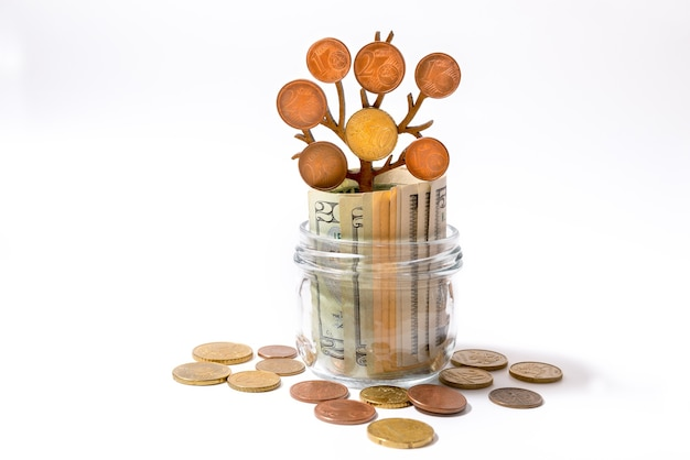 Een glazen pot met bankbiljetten uit de vs binnen en een groeiende boom met munten op de takken. investeringsconcept geldgroei. Premium Foto