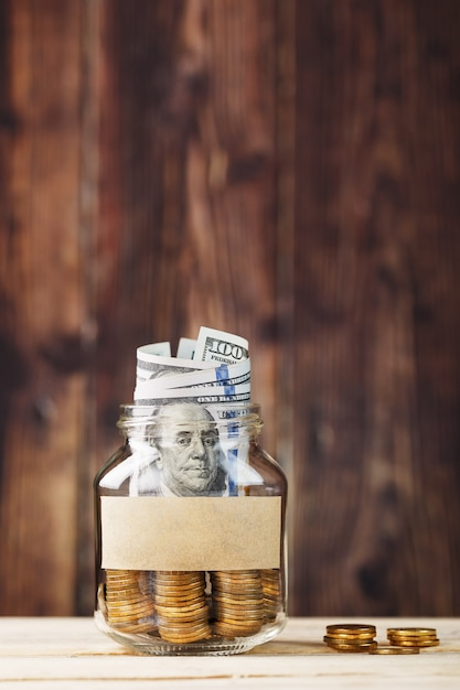 Een glazen pot met munten en een honderd dollar biljet, een sticker met vrije ruimte voor tekst, op een houten tafel. Premium Foto