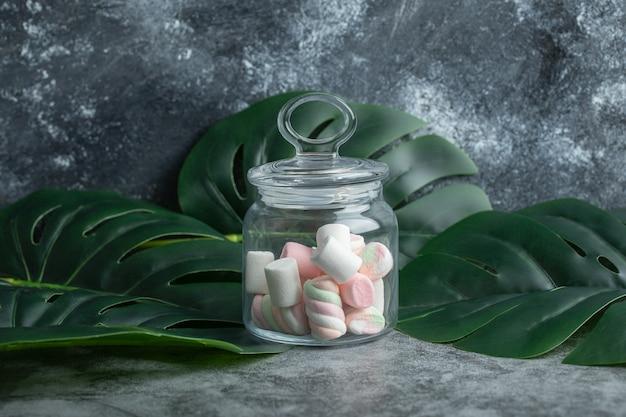 Een glazen pot vol marshmallows op bladeren. Gratis Foto