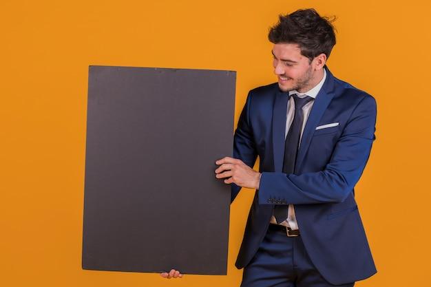 Een glimlachend jong zakenman die leeg zwart aanplakbiljet houdt tegen een oranje achtergrond Gratis Foto