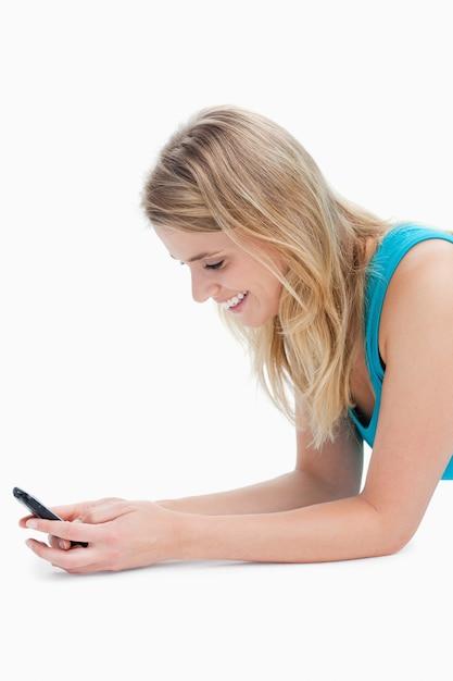 Een glimlachende vrouw texting op haar mobiele telefoon Premium Foto