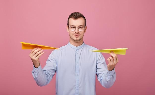 Een goed gefokte jongeman in blauw shirt en pc-bril staat met twee papieren vliegtuigen in zijn handen Premium Foto