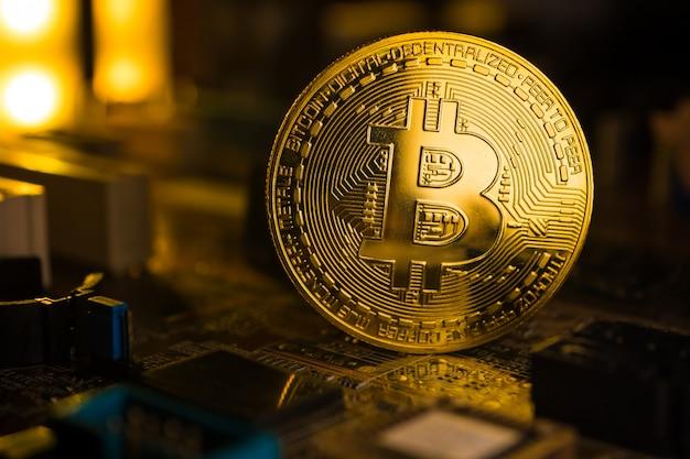 Een gouden munt met bitcoin symbool op een moederbord. Premium Foto