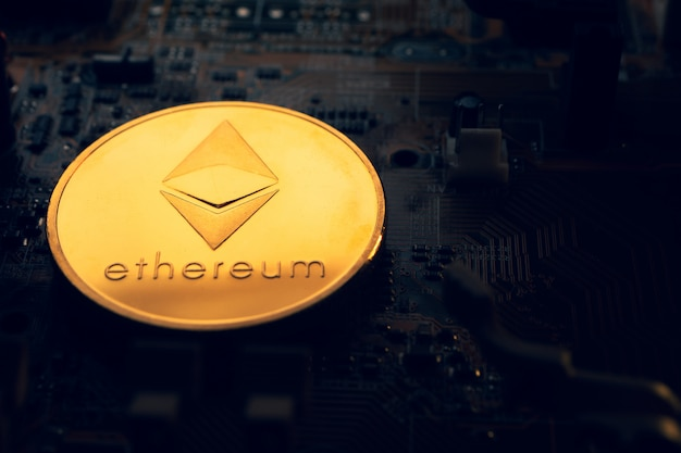 Een gouden munt met ethereum symbool op een moederbord. Premium Foto