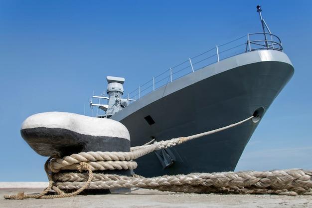 Een grijs modern oorlogsschip afgemeerd door touwen aan de kust. Premium Foto