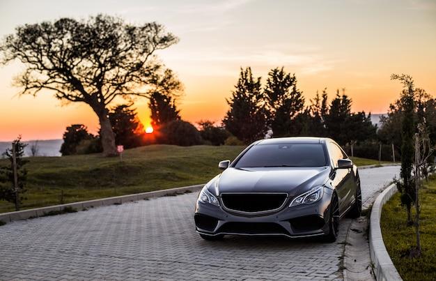 Een grijze auto van de luxesedan in de zonsondergang. Gratis Foto