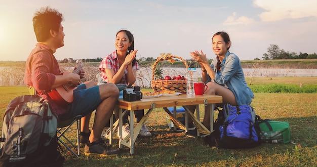 Een groep aziatische vrienden die ukelele spelen en tijd doorbrengen met een picknick in de zomervakantie. ze zijn gelukkig en hebben plezier op vakantie. Premium Foto