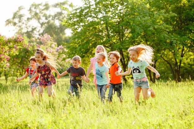 Een groep gelukkige kinderen van jongens en meisjes lopen in het park op het gras op een zonnige de zomerdag Premium Foto