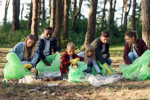 Een groep internationale vrijwilligers van meerdere leeftijd houdt de natuur schoon en haalt vuilnis op uit het bos. ecologie concept. Premium Foto