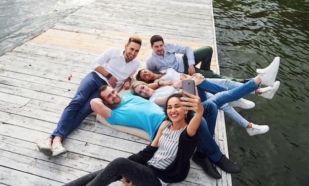 Een groep jonge mensen zit op de rand van de pier en maakt een selfie. vrienden die genieten van een spel op het meer. Gratis Foto