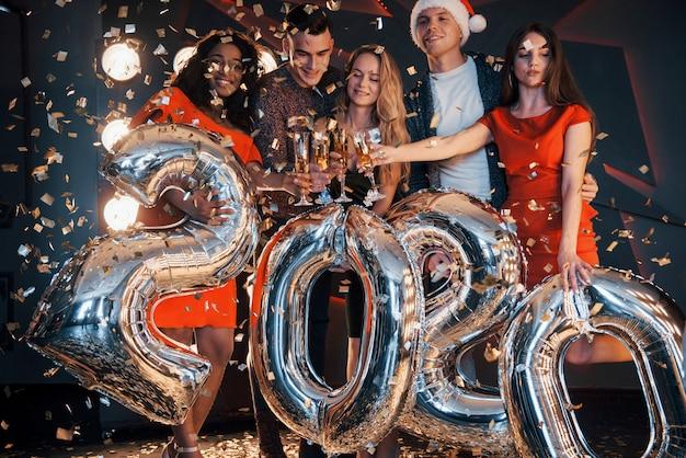Een groep leuke jonge mooie multinationale mensen die confetti gooien op een feestje. viering van 2020. Premium Foto