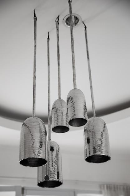 Een groep metaltische hangende lichten op wit plafond in loft ontworpen appartement. Premium Foto