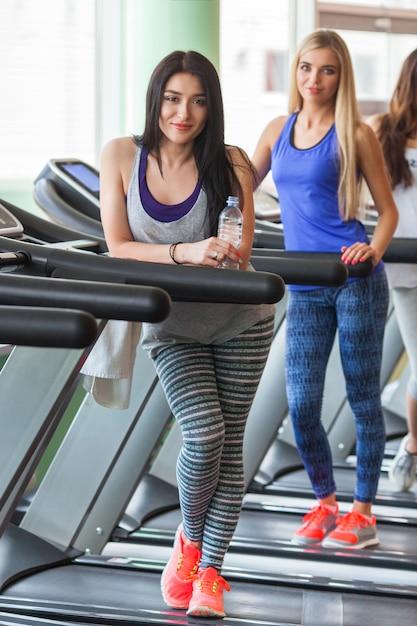 Een groep mooie meisjes in de goede vorm die op de loopbanden loopt. mooie vrouwen die in de gymnastiek opleiden. meisje lacht op camera Premium Foto