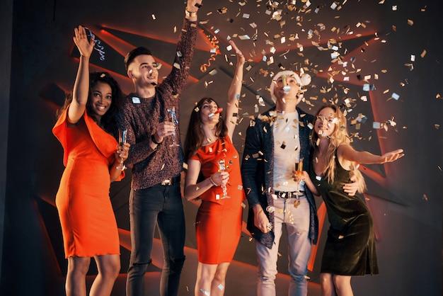 Een groep vrienden vermaakt zich in prachtige chiffon-jurken met champagne en confetti ter voorbereiding op het nieuwe jaar Premium Foto
