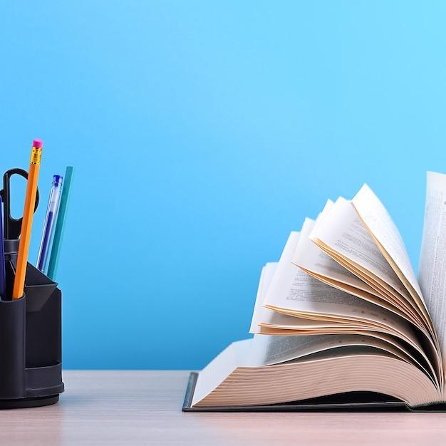 Een groot dik boek met de pagina's uitgespreid als een waaier en een standaard met pennen, potloden en schaar op de tafel op een blauwe achtergrond. Premium Foto