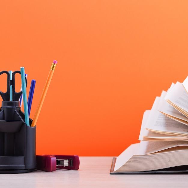 Een groot dik boek met de pagina's uitgespreid als een waaier en een standaard met pennen, potloden en schaar op de tafel op een oranje achtergrond. Premium Foto