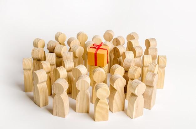 Een grote groep mensen omringt een doos met een cadeau. Premium Foto