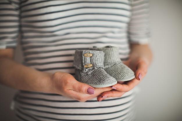 Een hand houdt een paar kleine schoenen vast. het zijn schoenen voor baby's. moeder en babythema. zwangere vrouw. geluk Premium Foto
