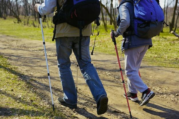 Een hart voor twee zwervers. leeftijd familie paar man en vrouw in toeristische outfit wandelen op groen gazon in de buurt van bomen in zonnige dag. concept van toerisme, gezonde levensstijl, ontspanning en saamhorigheid. Gratis Foto