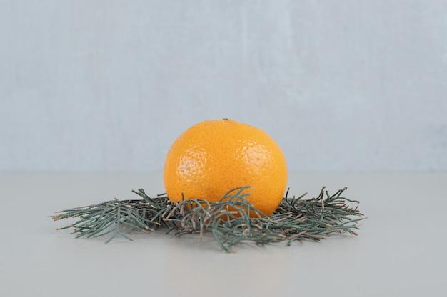 Een hele verse mandarijn op een grijze achtergrond. Gratis Foto