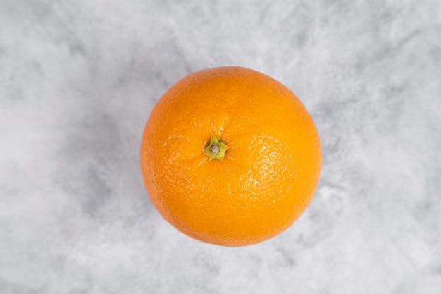 Een hele verse, sappige oranje vrucht op marmer Gratis Foto