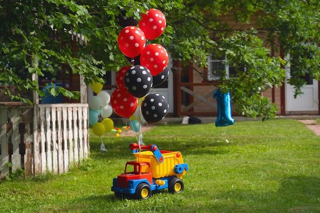 Een heleboel heliumballonnen zijn vastgebonden aan een grote speelgoedauto. verjaardagsfeest. Premium Foto