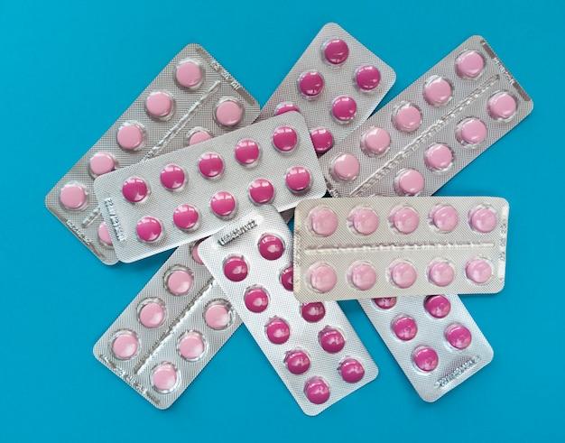 Een heleboel roze pillen in blaren op een blauwe achtergrond. medisch concept. Premium Foto