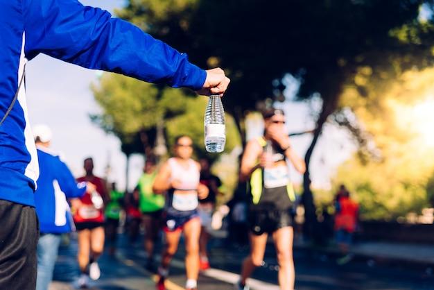 Een helpende hand levert een fles water aan een hardloper in een hardlooprace die hij kan drinken. Premium Foto