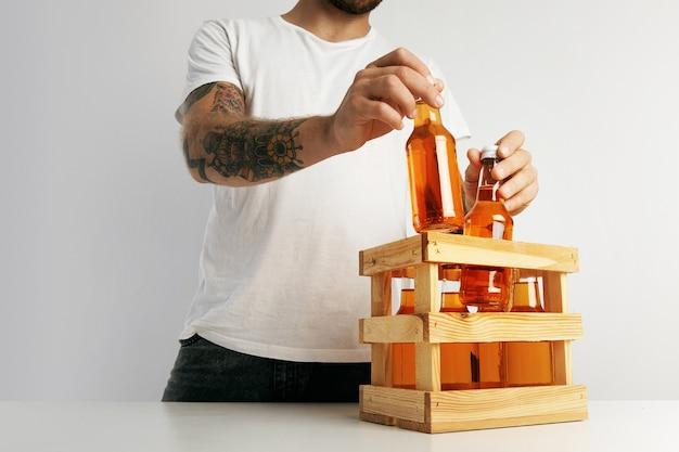 Een hipster in een effen wit t-shirt die flessen sinaasappellimonades inpakt in een houten kist op een witte tafel Gratis Foto