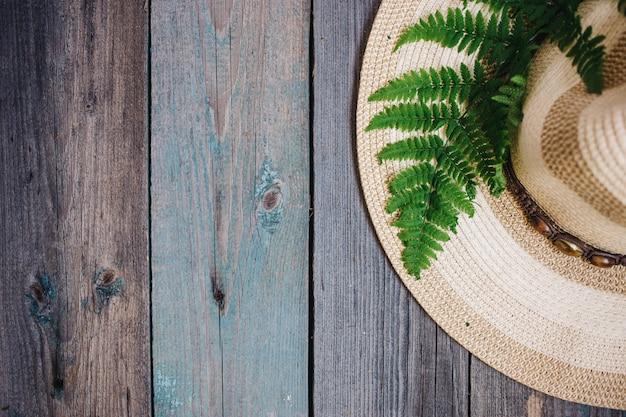 Een hoed, een varenblad op de houten achtergrond, exemplaarruimte Premium Foto