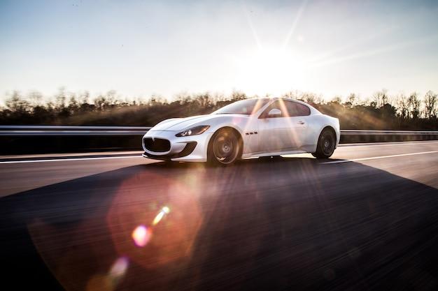 Een hoge snelheid zilveren sportwagen rijden op de snelweg in het zonnige weer. Gratis Foto