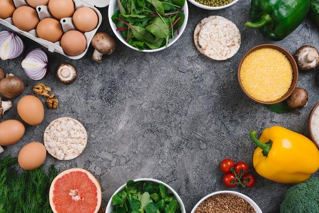 Een hoger beeld van groenten; walnoten; fruit en gepofte rijstwafel op grijze concrete achtergrond Gratis Foto