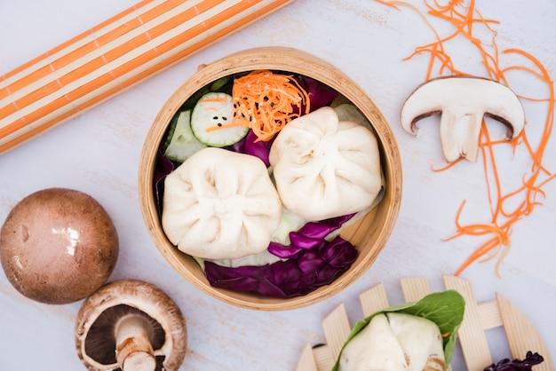 Een hoger beeld van stoomknoedels en salade in bamboestoomboot Gratis Foto