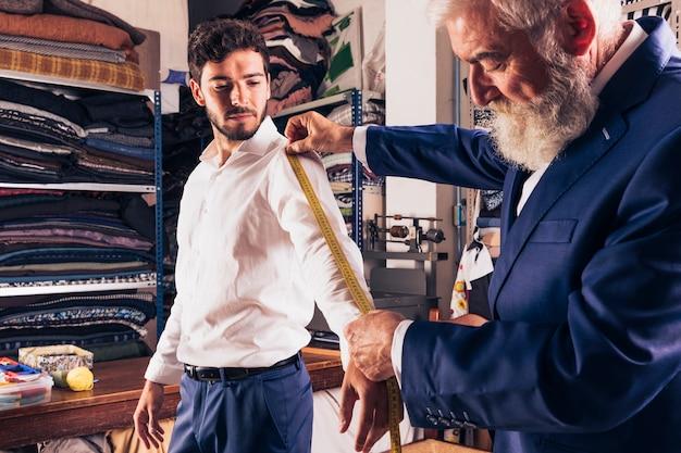Een hogere mannelijke manierontwerper die meting van zijn klantenkokers neemt Gratis Foto