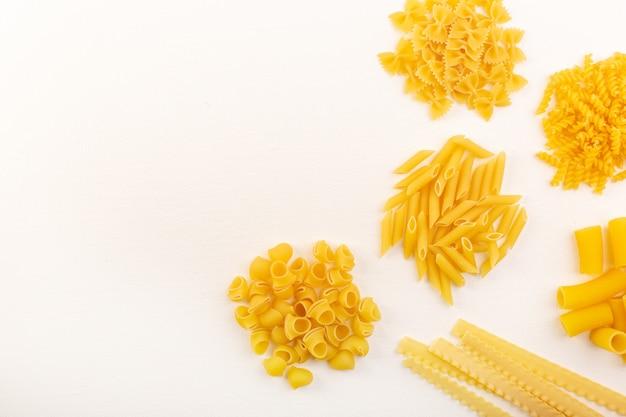 Een hoogste mening droge deegwaren droogt italiaanse gele deegwareninzameling en spreidt zich op de witte achtergrond italiaanse voedselmaaltijd uit Gratis Foto