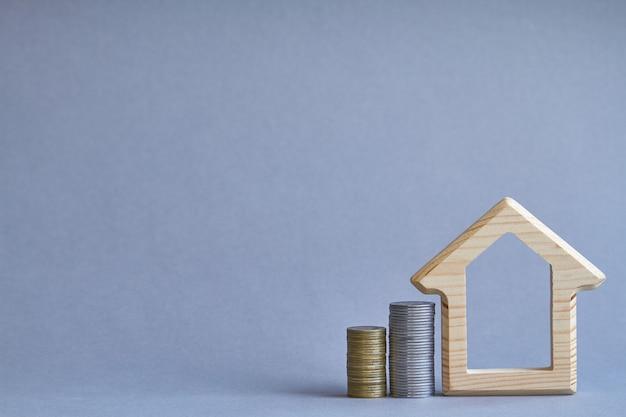 Een houten beeldje van een huis met twee kolommen met munten in de buurt op grijs Premium Foto