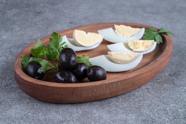 Een houten bord met olijven en gekookte eieren. hoge kwaliteit foto Gratis Foto