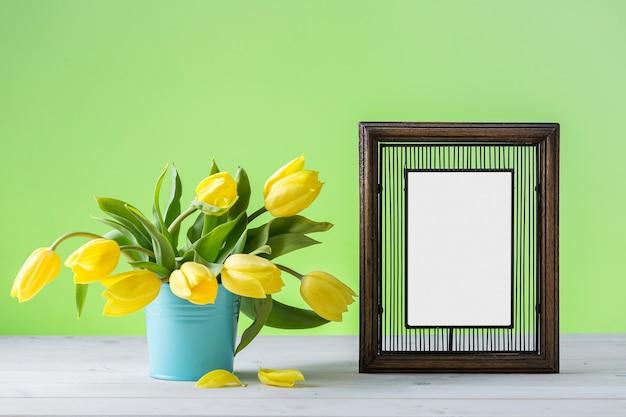 Een houten fotolijst in de buurt van gele tulpen op een houten oppervlak Gratis Foto