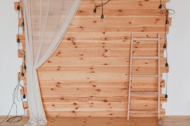 Een houten fotozone, versierd met hop, met gloeilampen en ladder. Gratis Foto