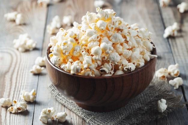 Een houten kom gezouten popcorn aan de oude houten tafel Premium Foto